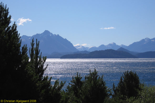 """Surrounded by mountains, Lago Nahuel Huapi in western Patagonia is stunningly beautiful. Luckily, the beauty of the area is protected by Lago Nahuel Huapi having been given national park status many years ago ― it is Argentina's oldest national park. However, the small city of San Carlos de Bariloche, which is the main tourism centre for """"Argentina's lake district,"""" is very busy in peak season (January-February), and is developing fast. The lake shore for miles either side of the city is littered with tourist cabanas and other buildings, not all of which are beautiful!"""