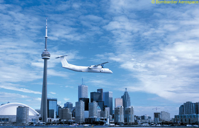 A Bombardier Q400 performs a low flypast over Toronto City Centre Airport, with the CN Tower and downtown Toronto forming a dramatic backdrop. Toronto City Centre Airport is the main hub of Porter Airlines, which operates an all-Bombardier Q400 fleet