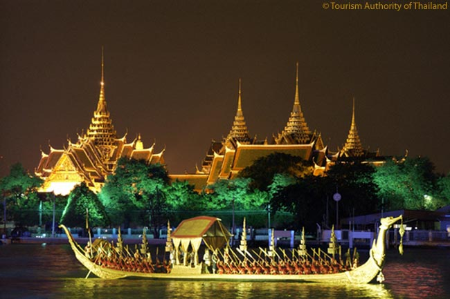 An ornate ceremonial boat glides along the Chao Phraya River, which runs through the heart of Thailand's capital Bangkok