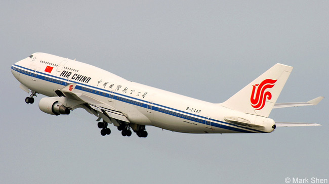 The landing gear retracts on an Air China Boeing 747-400 as the aircraft climbs away from the airport after taking off