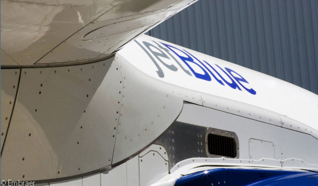 This is an unusual close-up shot of a JetBlue Airways Embraer 190 from the underside of its wing