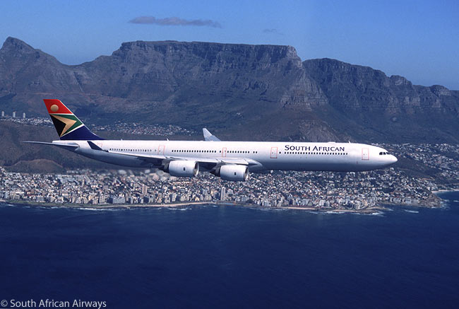 A South African Airways Airbus A340-600 flies off the coast of Cape Town, with Table Mountain prominently visible behind