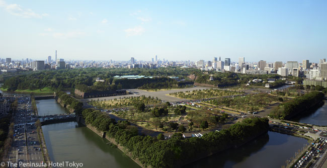 Upper levels of The Peninsula Hotel Tokyo have a magnificent view over Tokyo and the grounds of the Imperial Palace. In the middle distance can be seen the green roofs of the buildings of the Imperial Palace, surrounded by thick woods to allow Japan's emperor and his family a high degree of seclusion