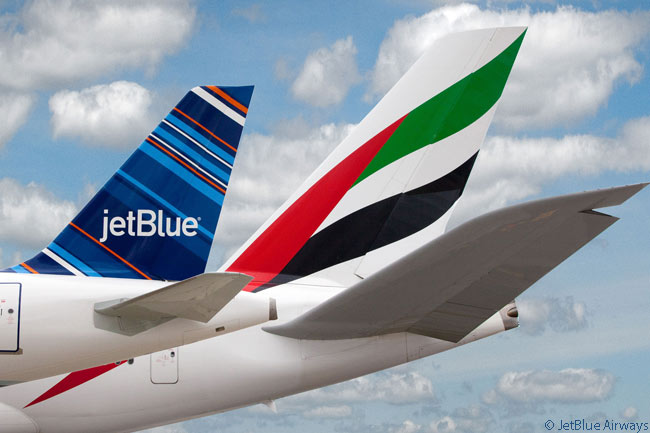 A JetBlue Airways Airbus A320 tail contrasts nicely in terms of color and size with the massive tail of the Emirates Airbus A380 superjumbo sitting behind it at New York JFK