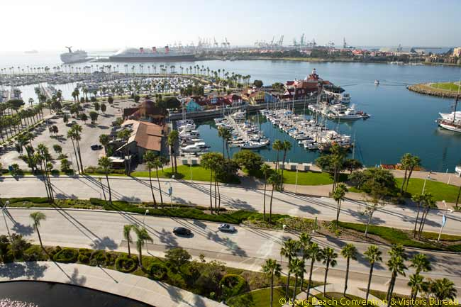 This photo, probably taken from an upper floor of the Long Beach Hyatt Regency, shows Rainbow Harbor to the right and Shoreline Village to the left. In the left forefront of the picture can be seen a small part of Rainbow Lagoon, behind which runs Shoreline Drive. In the distance the Queen Mary and the Long Beach Cruise Terminal are visible, beyond which lies part of the Port of Long Beach