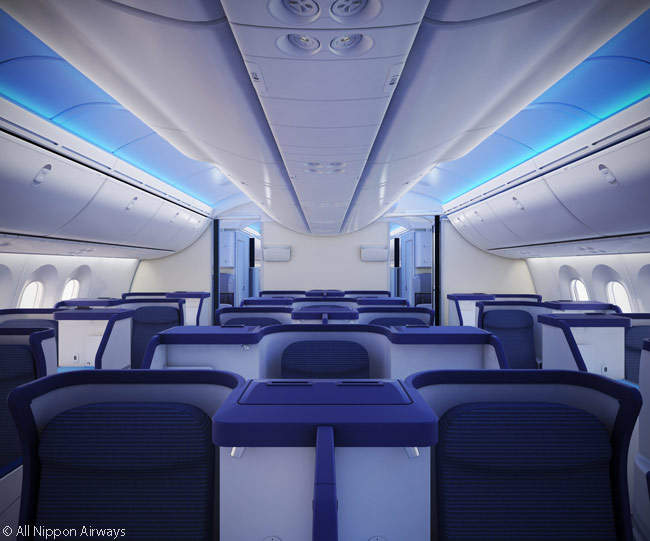 In ANA's Boeing 787 business class cabin, the ceiling is high and the overhead bins, especially by the windows, are large. The windows are oval-shaped and 1.3 times the usual size throughout the aircraft
