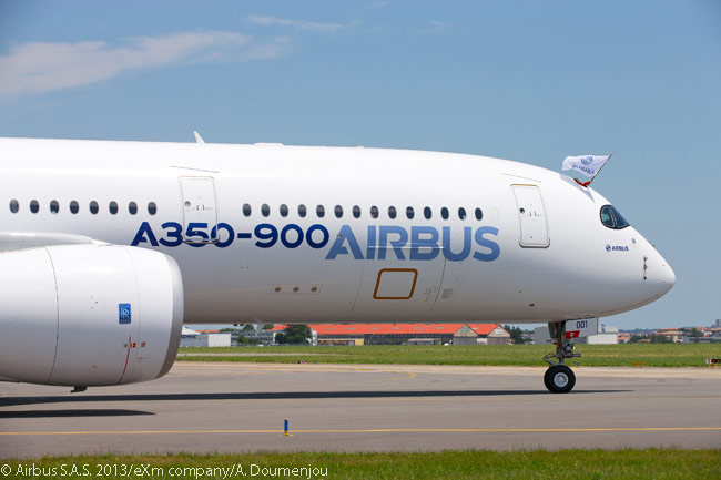 An Airbus flag flies from the open flight-deck hatch as A350 XWB MSN1 taxis to the Airbus Delivery Centre after landing following a successful maiden flight on June 14, 2013
