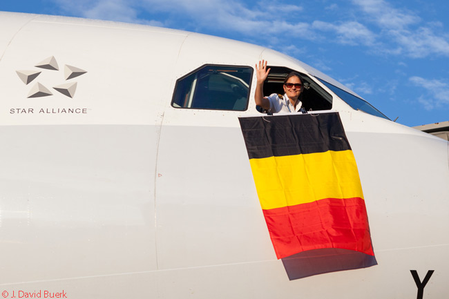 Sofie De Boever, the co-pilot on Brussels Airlines' inaugural Brussels-Washington Dulles flight on June 18, 2013, displays a Belgian national flag from an opened cockpit window as the Airbus A330-200 taxis towards its gate at Washington Dulles
