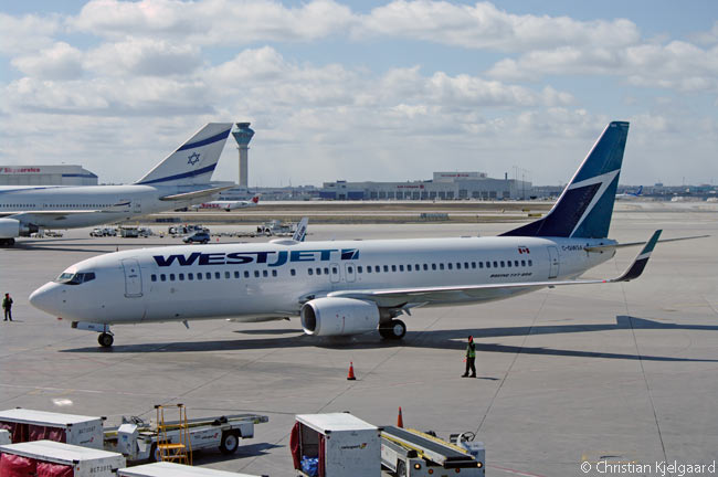 A WestJet Boeing 737-800 taxis in towards its gate at Toronto Pearson International Airport's Terminal 3