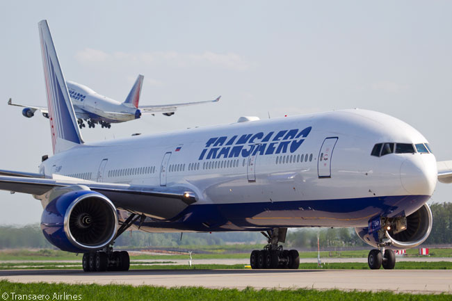 Russia's Transaero Airlines operates 14 Boeing 777s. Five are ex-Singapore Airlines 777-300s (these are of the original, non-ER model) and nine are 777-200ERs. This photograph shows one of Transaero's 777-300s, with one of the airline's Boeing 747-400s taking off in the background