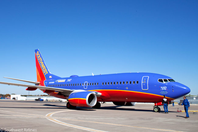 A Southwest Airlines Boeing 737-700 pushes back from a gate at Dallas Love Field, where the airline's headquarters are located