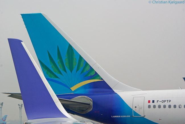 Air Caraïbes' very attractive livery evokes the turquoise waters and palm trees of the Caribbean, as seen on the vertical stabilizer of this Air Caraïbes Airbus A330-200 at Paris Orly Airport. The photograph was taken from inside the cabin of a Boeing 757 of the firmer all-business-class airline L'Avion (which had a similarly memorable, all-violet livery) and one of the 757's violet-colored winglets can be seen in the photograph