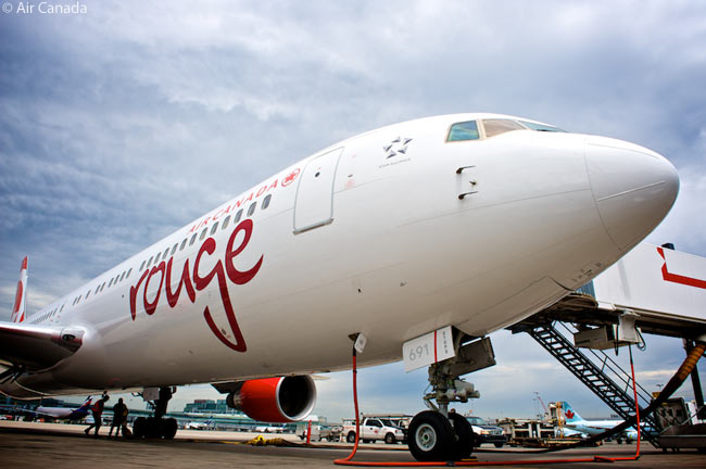 An Air Canada rouge Boeing 767-300ER is serviced at the gate at Montreal's Pierre Elliot Trudeau International Airport before its forthcoming flight
