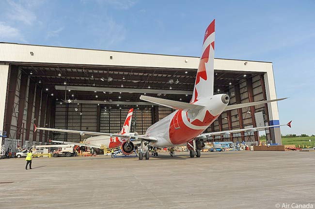 Two Air Canada rouge Airbus A319s are photographed while being serviced at an Air Canada maintenance hangar