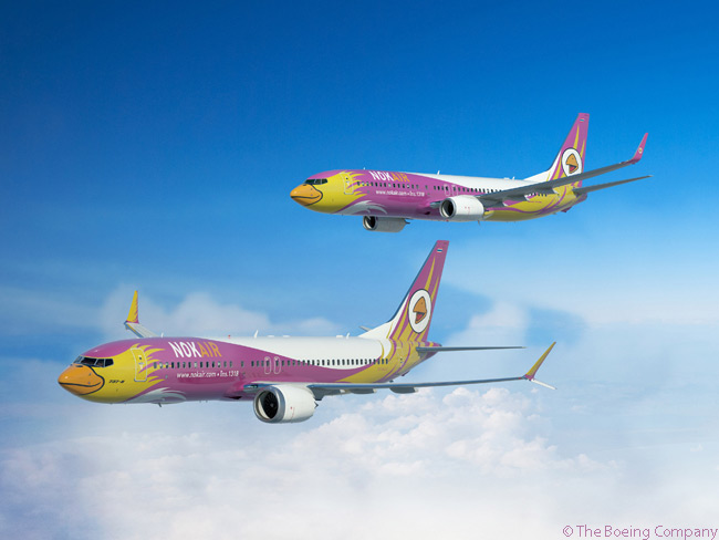 On February 12, 2014, at the Singapore Airshow 2014, Nok Air signed a commitment to order eight Boeing 737-800s and seven Boeing 737 MAX 8s. In doing so Nok Air became the first airline based in Thailand to commit to ordering the Boeing 737 MAX. This computer graphic image shows a Boeing 737 8 MAX (foreground) and 737-800 (background) in Nok Air's colorful bird livery