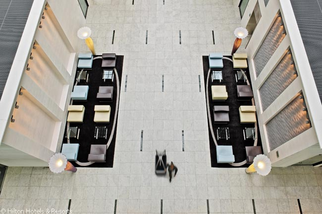 From the hotel's glass-walled elevators, guests get the best impression of the large open volume of the Hilton Frankfurt Airport's lobby area