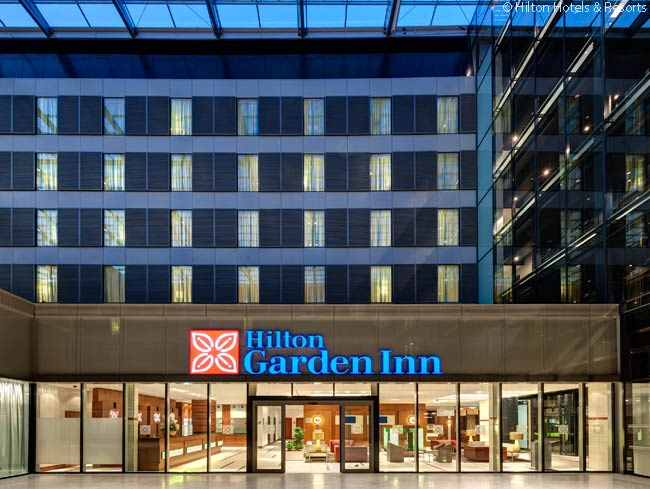 The entrance to the Hilton Garden Inn Frankfurt Airport is at the northeast end of the hotel, which is located next to the Hilton Frankfurt Airport on an upper plaza level above the inter-city rail station in The Squaire building near Frankfurt Airport. Unusually, the Hilton Garden Inn occupies both the northern and southern sides of the plaza. Guests get from the entrance to rooms on the other side of the plaza via an overhead footbridge