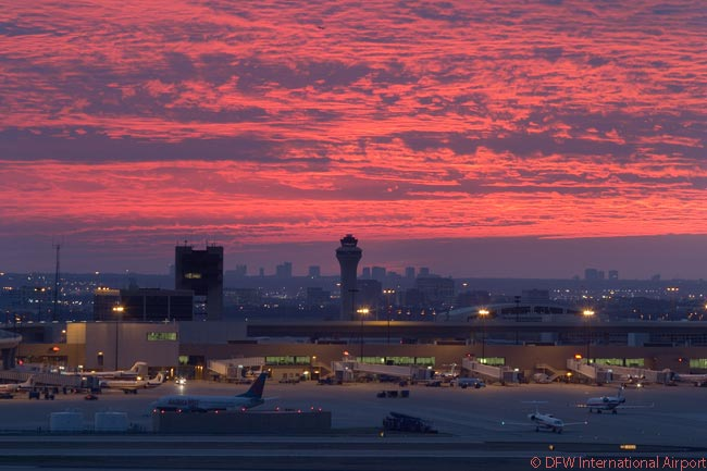 A vivid sunrise over Dallas/Fort Worth International Airport's Terminal B heralds a new day of operations at the huge, seven-runway airport, which is the third-busiest in the world in terms of aircraft movements