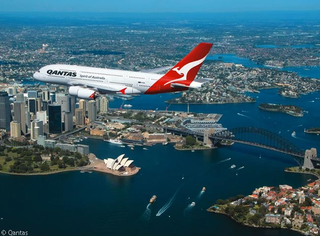 During an air-to-air photography session, a Qantas Airbus A380 flies over the famous Sydney Opera House and Sydney Harbour Bridge in the heart of Sydney's downtown area