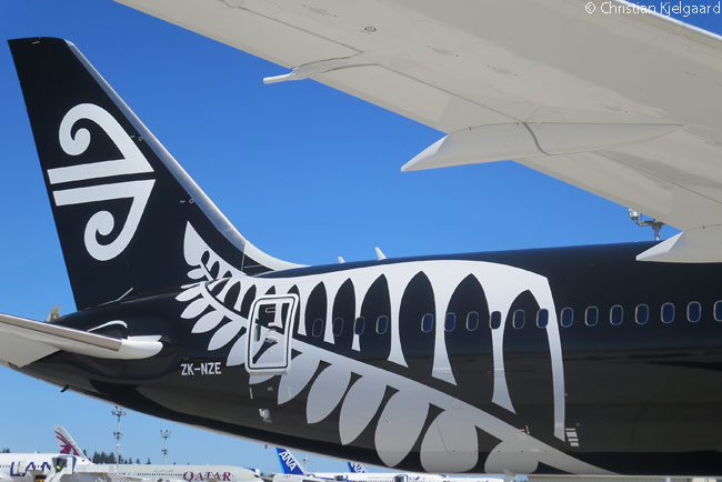 Air New Zealand's white logo (which is a Maori koru symbol) on the vertical stabilizer, and the national silver fern symbol of New Zealand on the rear fuselage, are prominent against the 'All Black' livery of its first Boeing 787-9