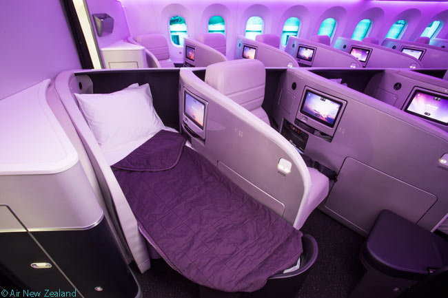Air New Zealand's long-haul Business Premier-class armchair folds down into a 79-inch flat bed. Note the partially dimmed windows, which become somewhat turquoise, in this photograph of the interior of the airline's first Boeing 787-9