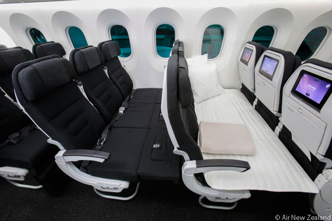 This photo shows two Economy class Skycouch seat rows on Air New Zealand's first Boeing 787-9. The first row shows the Skycouch with the mattress placed on top for sleep, while the second row shows the Skycouch without the mattress but with the bases of the seats brought up to provide lounging space for children or adults