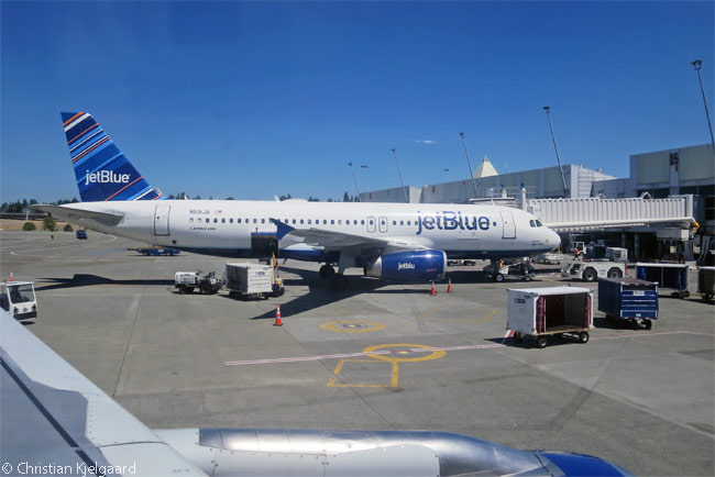 A JetBlue Airways Airbus A320 is photographed docked at gate D5 at Seattle-Tacoma International Airport from exit-row window seat 10A on another JetBlue A320, which was departing from gate D4