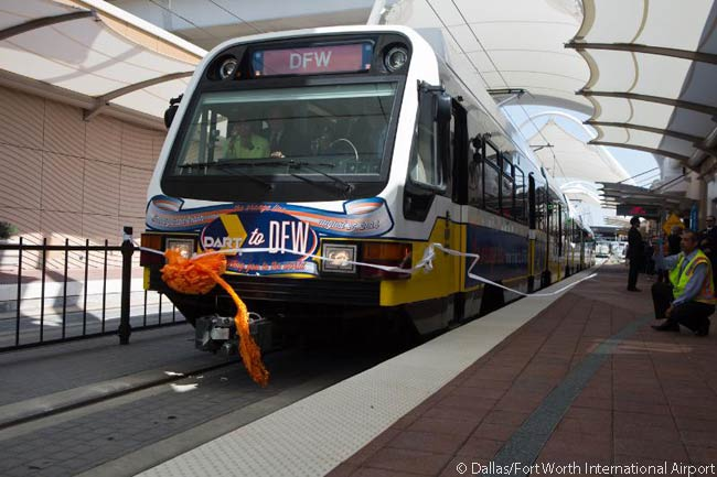 The first Dallas Area Rapid Transit (DART) light-rail train ever to serve Dallas/Fort Worth International Airport pulls into the airport station. Its arrival at 3:50 a.m. on August 18, 2014 represented the culmination of a six-year effort by the two organizations to build the five miles of DART Orange Line track needed to complete the rail link from downtown Dallas to the airport