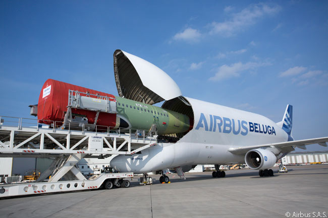 In this photograph, one the five first-generation Beluga outsize-cargo transporter aircraft developed from A300-600 airframes by Airbus loads the fuselage of the first Airbus A320neo at Airbus' plant at Finkelwerder Airfield near Hamburg. The aircraft then flew the fuselage to Airbus' Toulouse facility for final assembly of the first A320neo