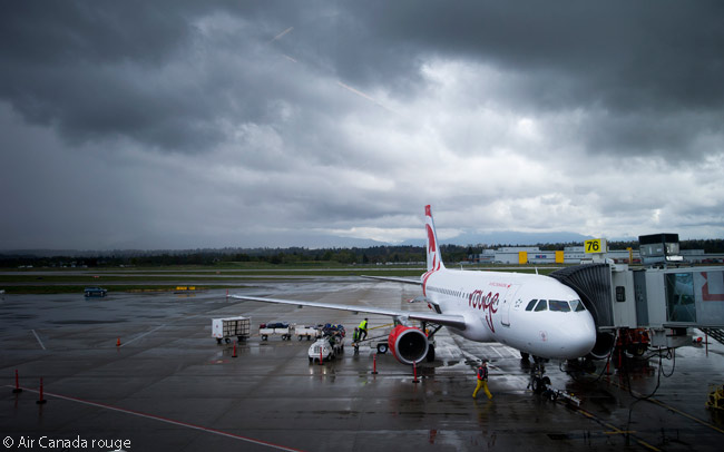 An Air Canada rouge Airbus A319 is prepared for its next departure at a Canadian airport on a gray and rainy day, against the backdrop of a dramatic sky