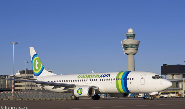 Most of Transavia Company's aircraft are based at Amsterdam Airport Schiphol, the control tower of which can be seen behind this Boeing 737-800