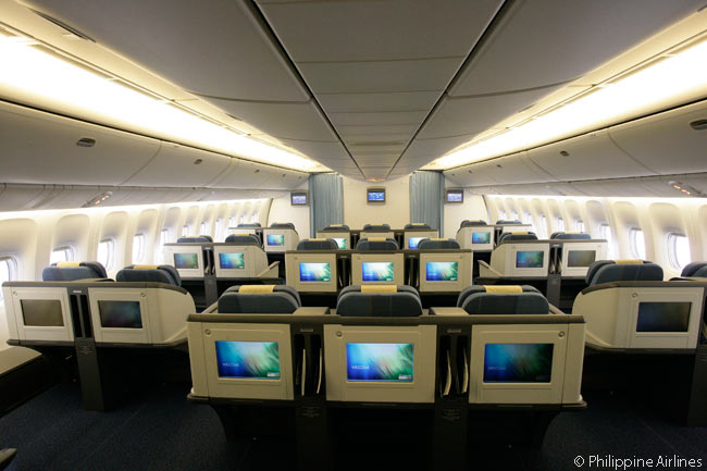 This is a view from behind of part of the Business Class cabin in a Philippine Airlines Boeing 777-300ER. Unusually, the center seat block has three seats instead of the more usual two or four