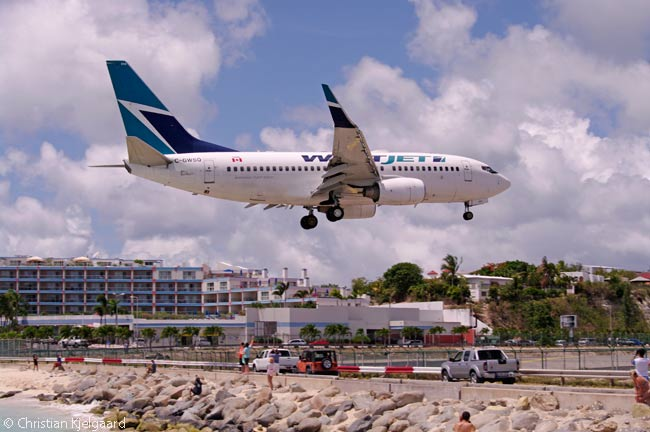 Sint Maarten's SXM Airport is served by Canadian carriers Air Canada, WestJet and Sunwing Airlines. In this photo, a WestJet 737-700 crosses over the permiter fence on very short final to SXM's Runway 10