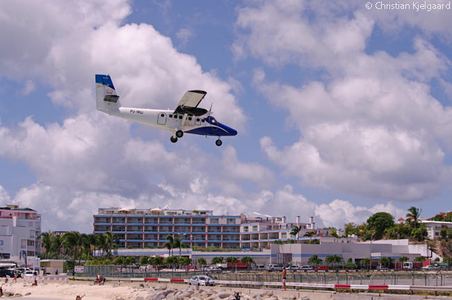 Locally based carrier Winair, the national airline of Sint Maarten, operates downs of flights daily to and from Proncess Juliana International Airport. Here, Twin Otter PJ-WIJ flies over Maho Beach on its final approach to Runway 10 at SXM Airport