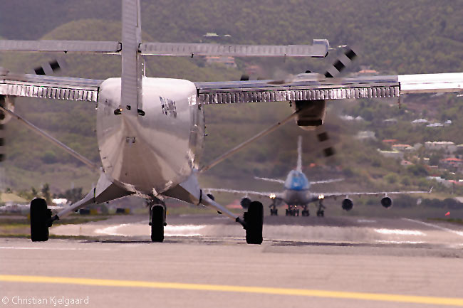 A Winair Twin Otter lines up for take-off on Runway 10 at Sint Maarten's Princess Juliana International Airport as a KLM Boeing 747-400 taxis back along the runway after landing