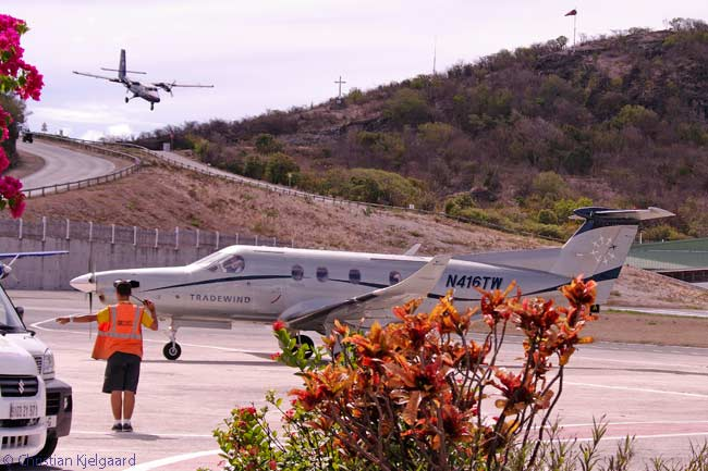 A Winair Twin Otter flies down the 146-foot-high hill which forms the last part of the approach to Gustaf III Airport on the Caribbean island of Saint Barthélemy
