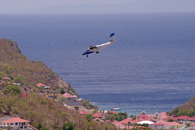 This photo shows a Winair Twin Otter performing 'The Saint Barth Dive': an approach at a 10-degree angle to the island's Gustaf III airport. The dive is possibly the most steeply angled approach to any commercial airport in the world