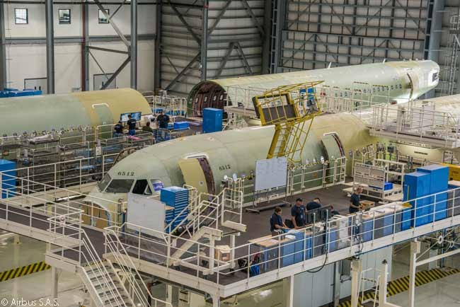 Major components of the first two aircraft (both A321s) to be assembled at the Airbus A320 final-assembly line in Mobile, Alabama are seen in the main final assembly hangar. The aircraft in the forefront, the first aircraft to be assembled, was destined for JetBlue Airways and the one behind it for American Airlines