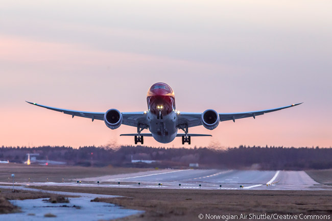 This dramatic shot captures a Norwegian Boeing 787-8 moments after take-off from what appears to be a relatively short runway