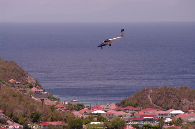A Winair Twin Otter Series 300 performs the famous 'Saint Barth Dive' 10-degree final approach to landing at Saint Barth's Gustaf III Airport