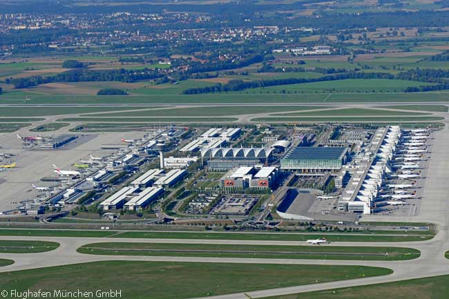 This aerial photo shows Munich Airport's central area. Terminal 1 is at left center and Terminal 2 at right center. The new Terminal 2 Satellite is located off to the right of the right edge of the photo. Runway 08L/26R, the airport's northern parallel runway, can be seen running across the upper center of the photograph